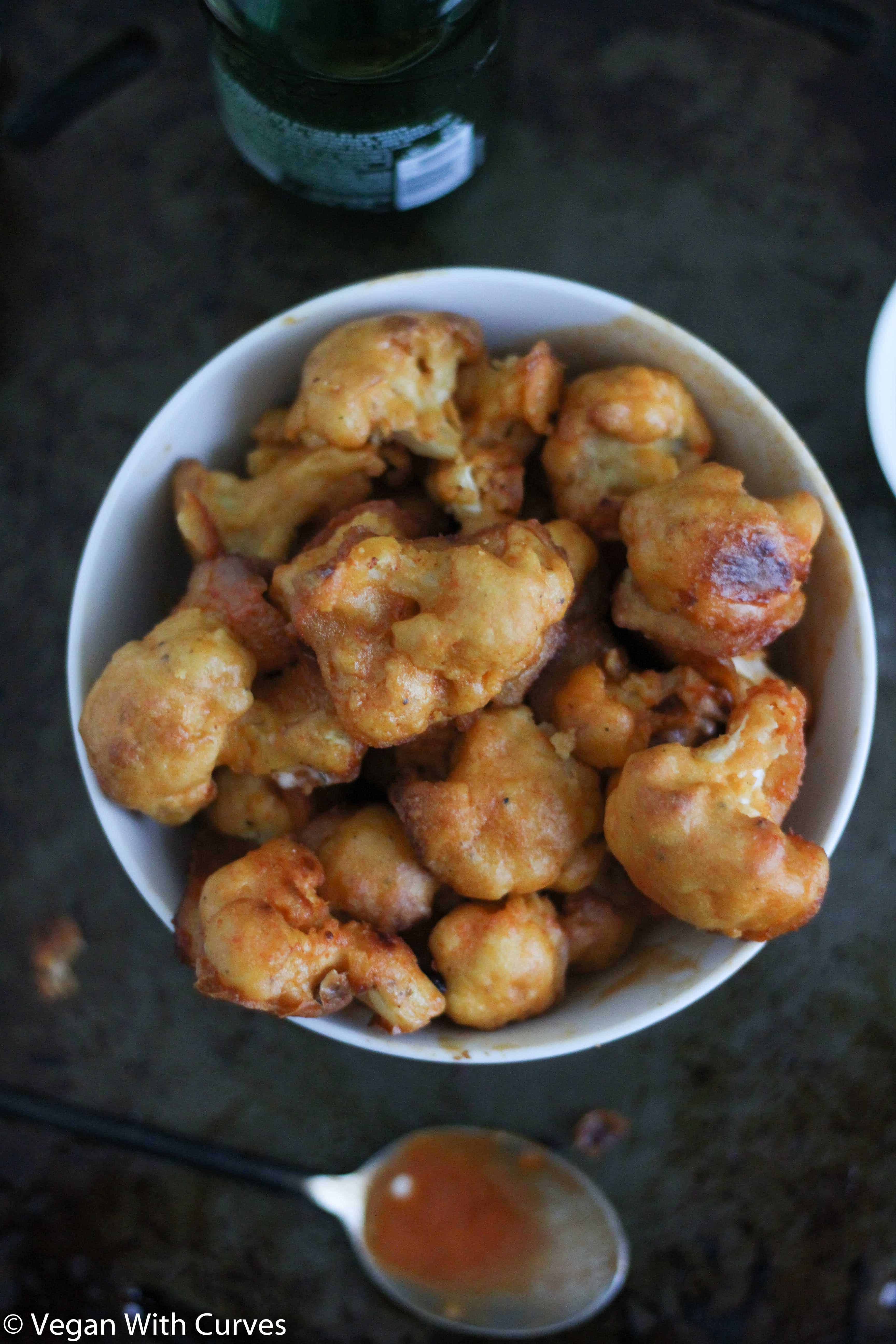 close up shot of baked cauliflower bites in a white bowl next to a beer bottle