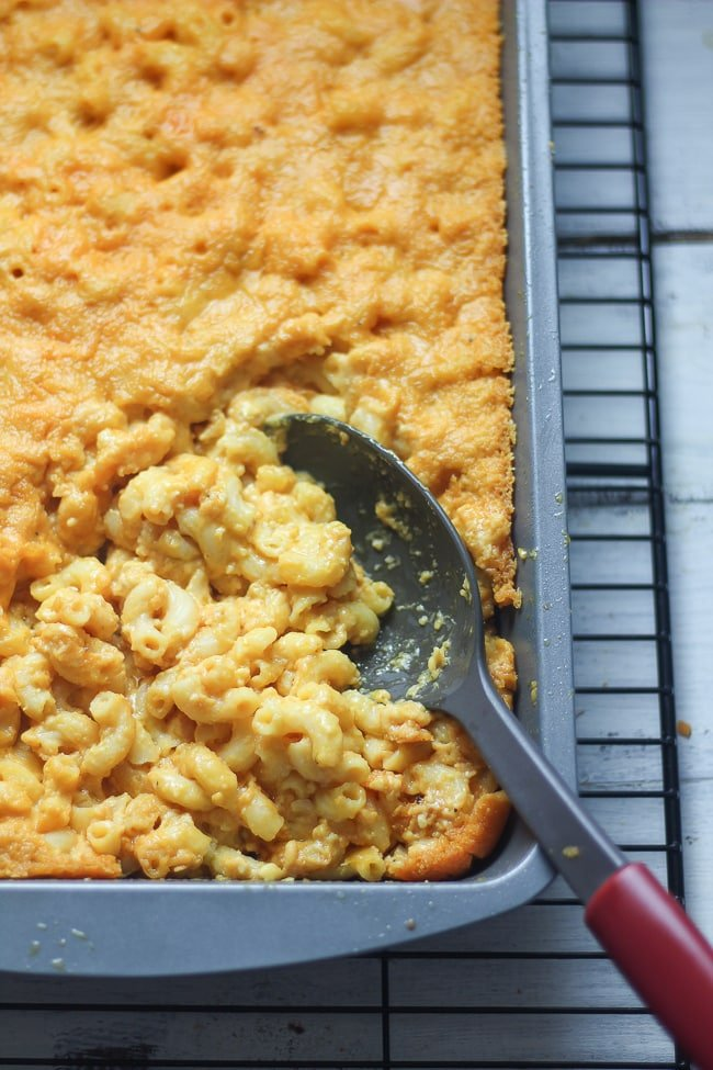 baked vegan mac and cheese in a pan being scooped into