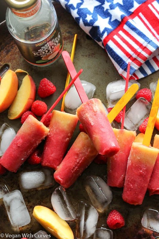 homemade popsicles laying on top of ice with raspberries and peaches