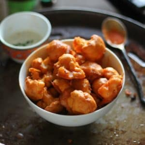 baked buffalo cauliflower in a white bowl