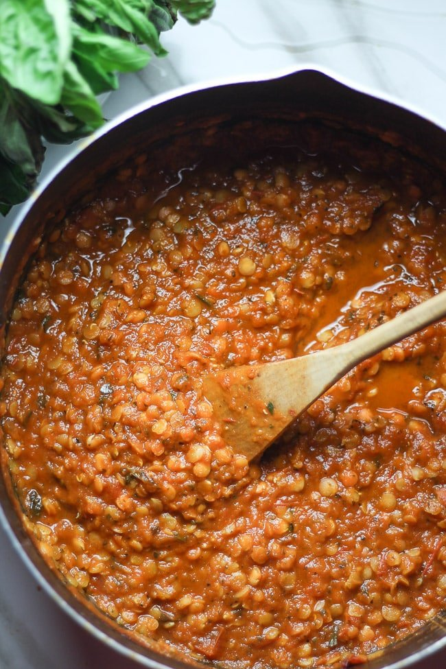 lentil tomato sauce in a pot with wooden ladle