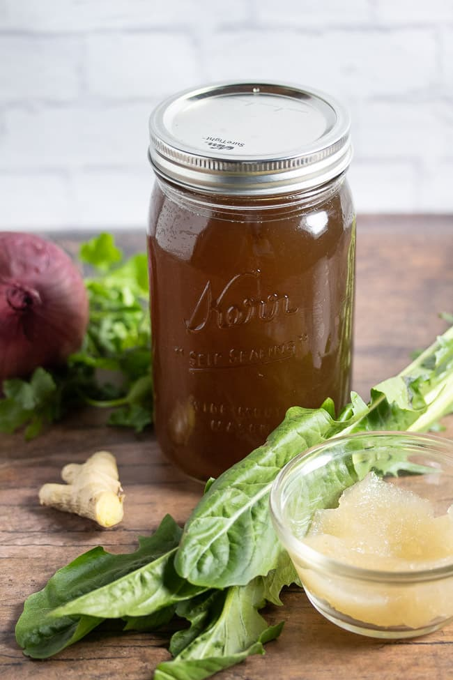 top angle vegan broth in a mason jar on a table with vegetables and sea moss gel