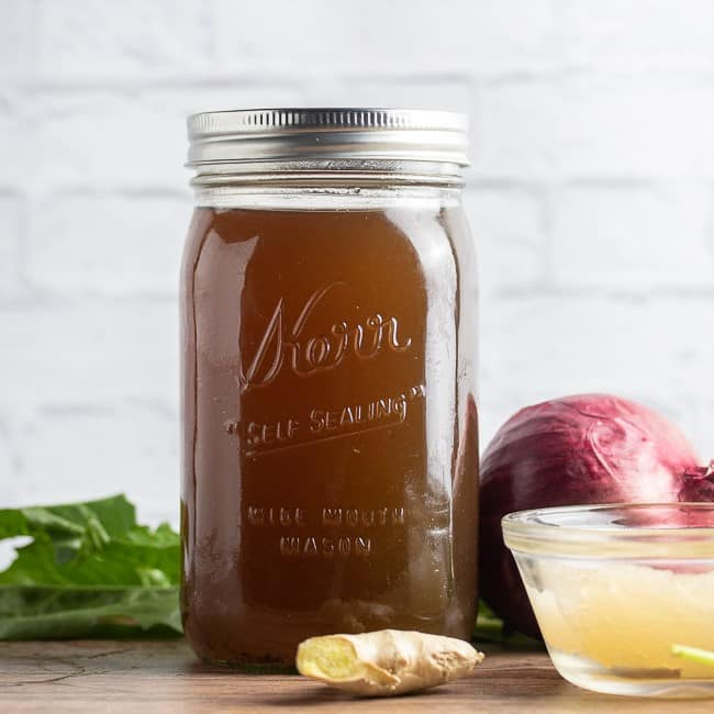 vegan broth in a mason jar on a table with vegetables and sea moss gel