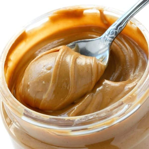 jar of creamy peanut butter with spoon it to reference calorie dense foods