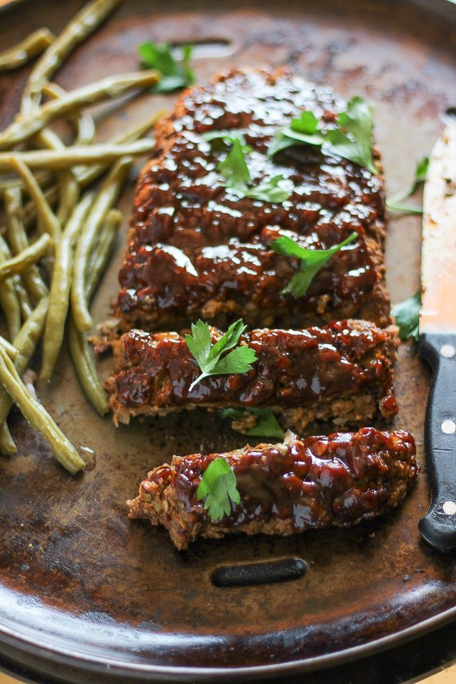 different angle of vegan meatloaf cut with 2 slices cut from the loaf next to green beans on a baking pan