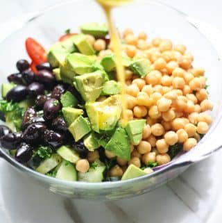 cucumber chickpea tomato salad unmixed pouring salad dressing over it