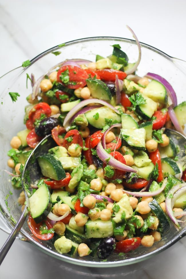 mixed up cucumber chickpea tomato salad in a large mixing bowl