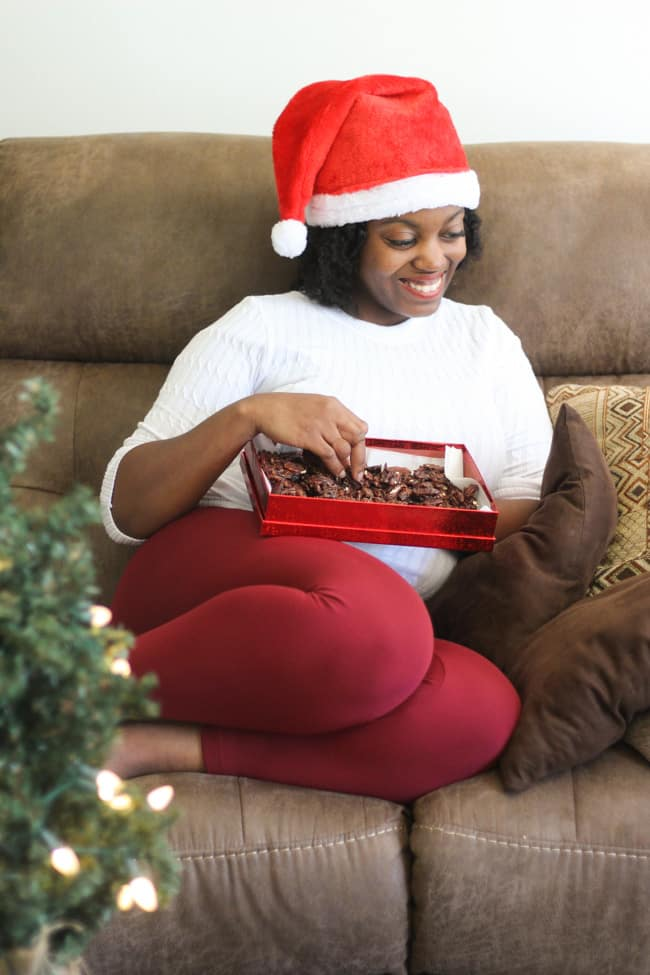 Gina Marie from Vegan With Curves sitting on a couch with a Christmas hat eating candied pecans