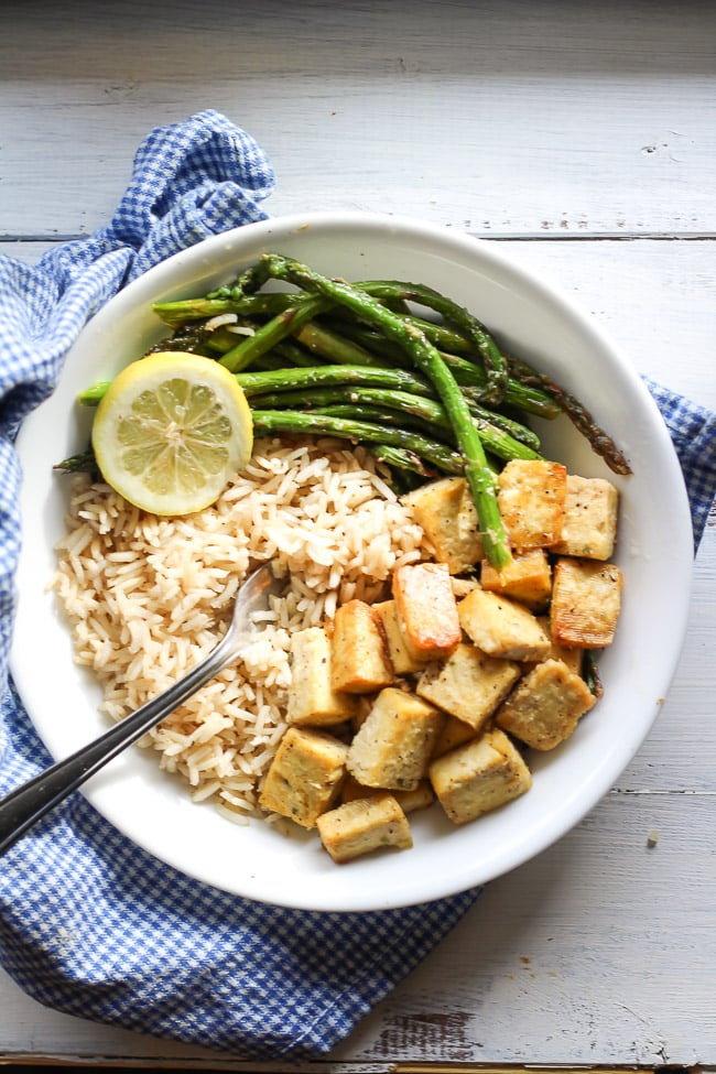 a picture of tofu, brown rice, and asparagus in a white bowl bowl with fork and lemon slice
