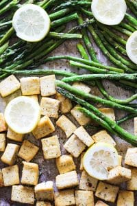 a picture of baked tofu and asparagus on a sheet pan with slice lemons