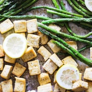 tofu and asparagus on a sheet pan with slice lemons