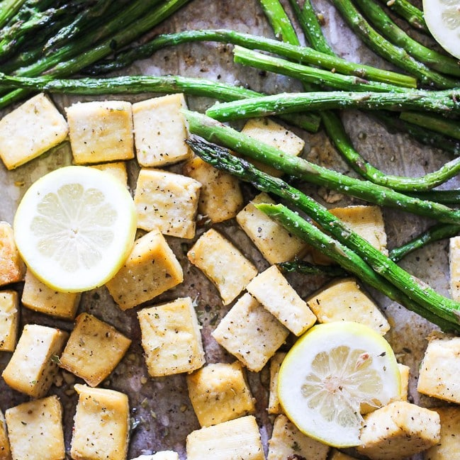 tofu and asparagus on a sheet pan with slice lemons
