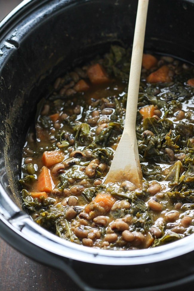 black-eyed pea soup in a slow cooker with wooden ladle