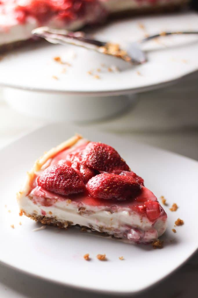 slice of strawberry vegan cheesecake on a plate