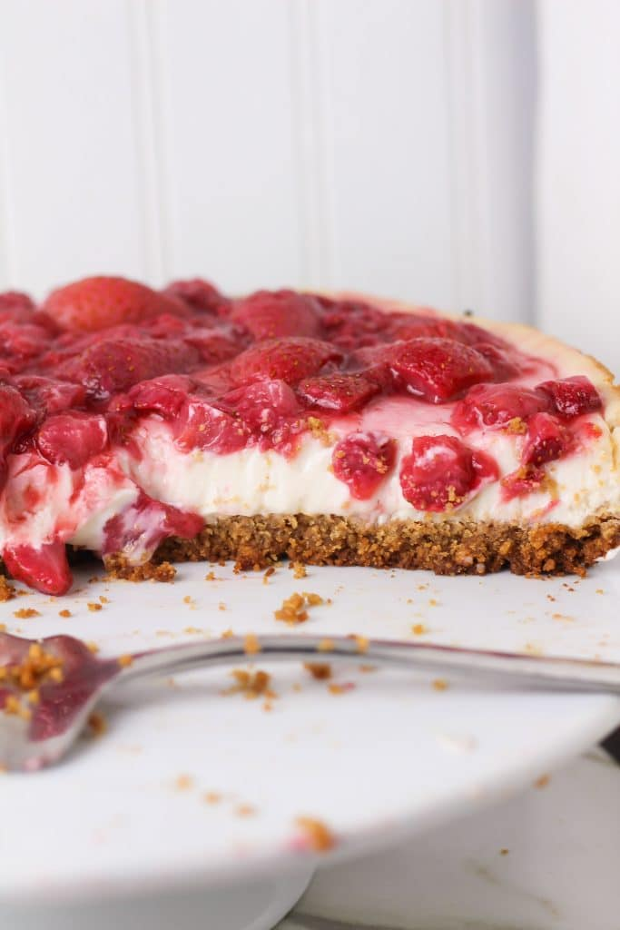 strawberry vegan cheesecake pie sliced from pie showing at a side angle