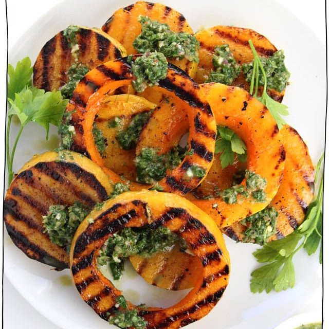 grilled butternut squash on a plate topped with chimichurri sauce