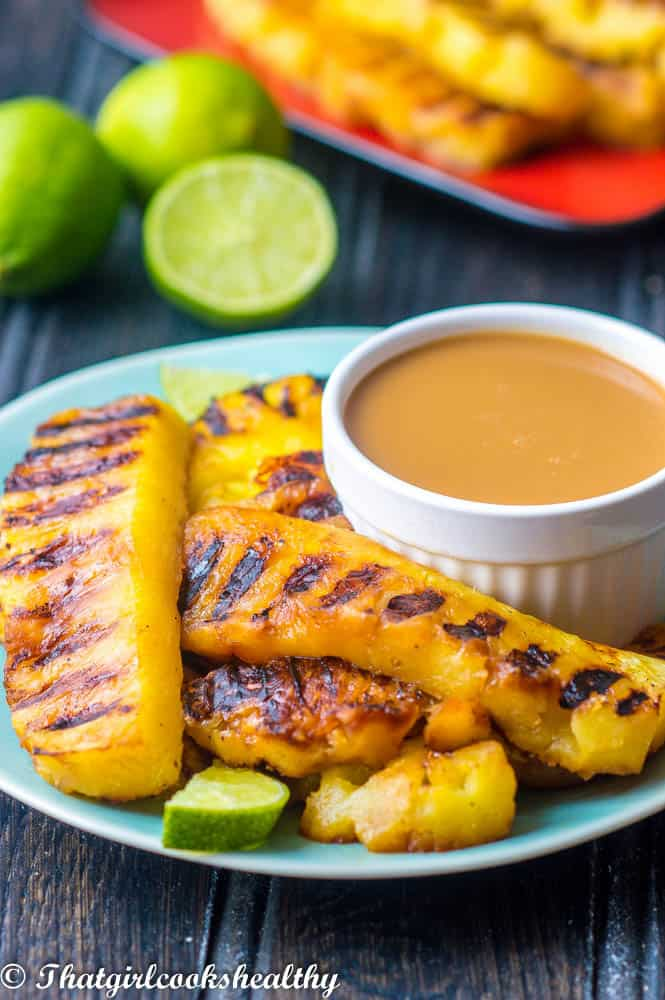 sliced grilled pineapples on plate with rum dip