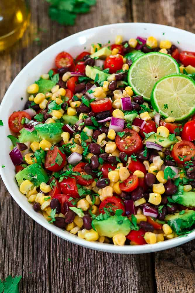 avocado black bean corn salad in on a white plate with 2 slice limes