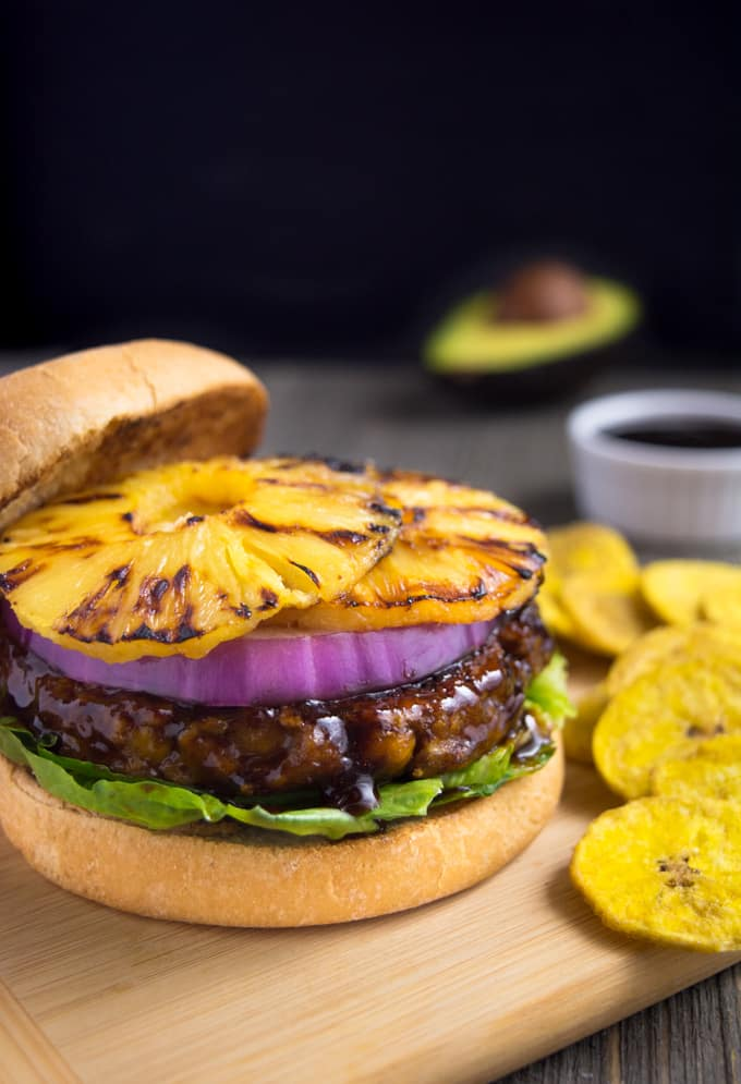 vegan huli-huli vegan burger topped with grilled pineapple ring and onion on a bun