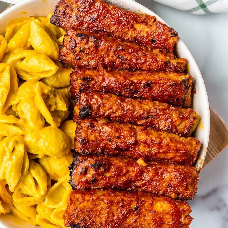 vegan tempeh ribs on a white plate next to vegan mac and cheese