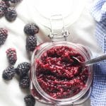 blackberry jam in glass jar with spoon in it