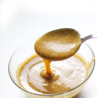 date caramel sauce dripping from a spoon into a bowl