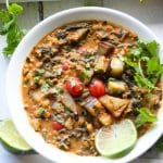 coconut lentil curry in a white bowl with sliced lime