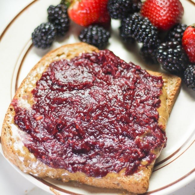 blackberry jam spread over walnut butter and bread