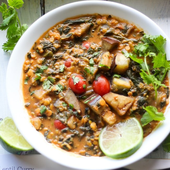 red lentil curry in a white bowl with lime slice and cilantro