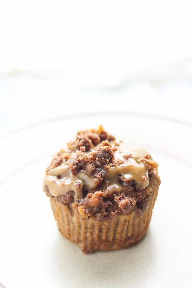 one muffin on a plate topped with vegan caramel sauce