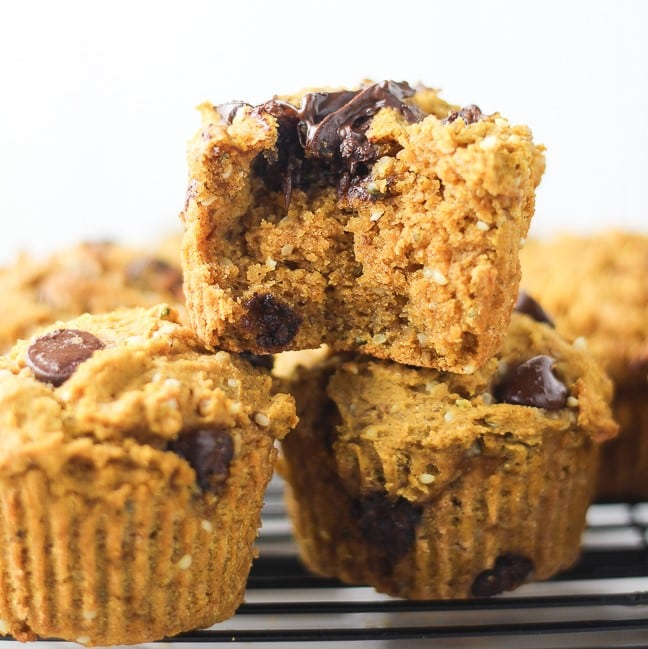 one muffin bitten into sitting on top of 2 muffins