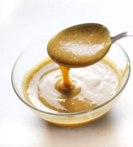 caramel sauce dripping from a spoon into a bowl