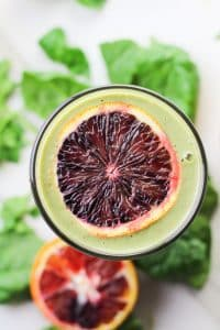 overhead shot of a green smoothie in glass with slice blood orange on top