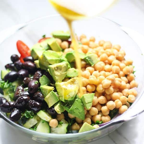 picture of salad with avocado, olives and oil dressing being poured