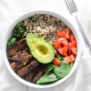 tempeh bacon, spinach, quinoa, kale tomatoes and half of avocado slice in a white bow with fork