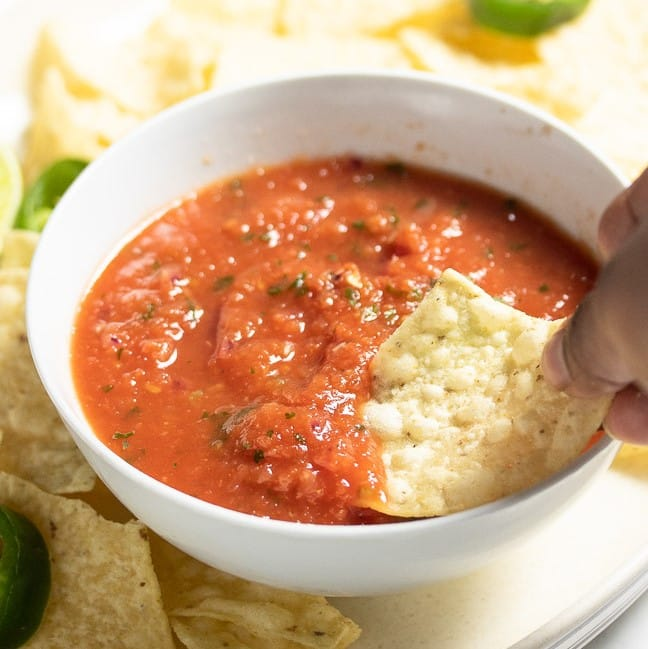 red vegan salsa in a white bowl with chip being dipped into it