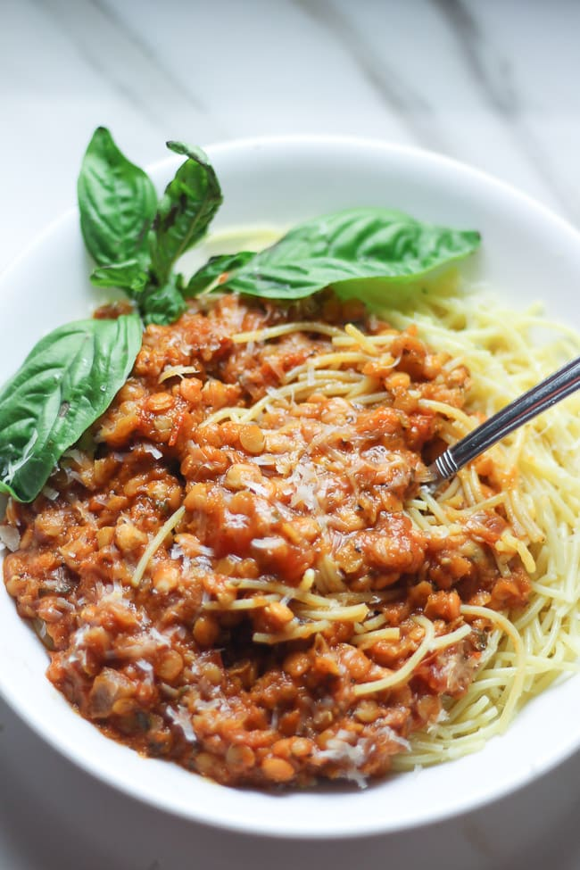 red lentil tomato sauce on top of spaghetti pasta with fresh basil on a white plate with a fork