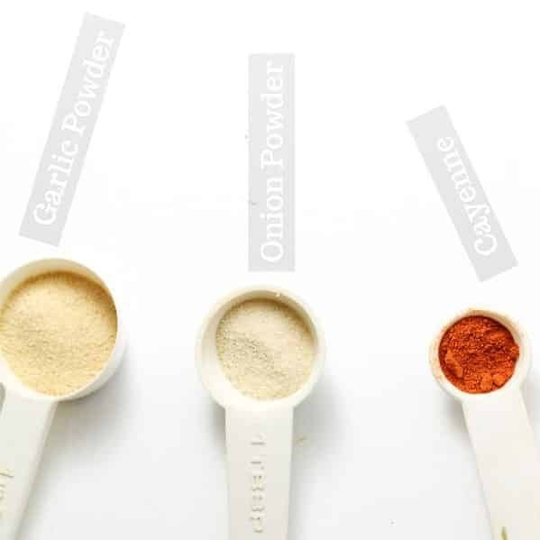 picture of garlic powder, onion powder, and cayenne powder in separate measuring teaspoons