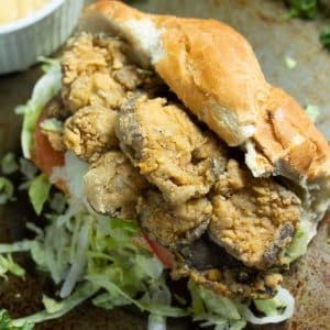 fried oyster mushrooms sandwich with french bread topped with lettuce and tomatoes