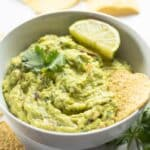 guacamole in a white bowl with tortilla chip and lime slice