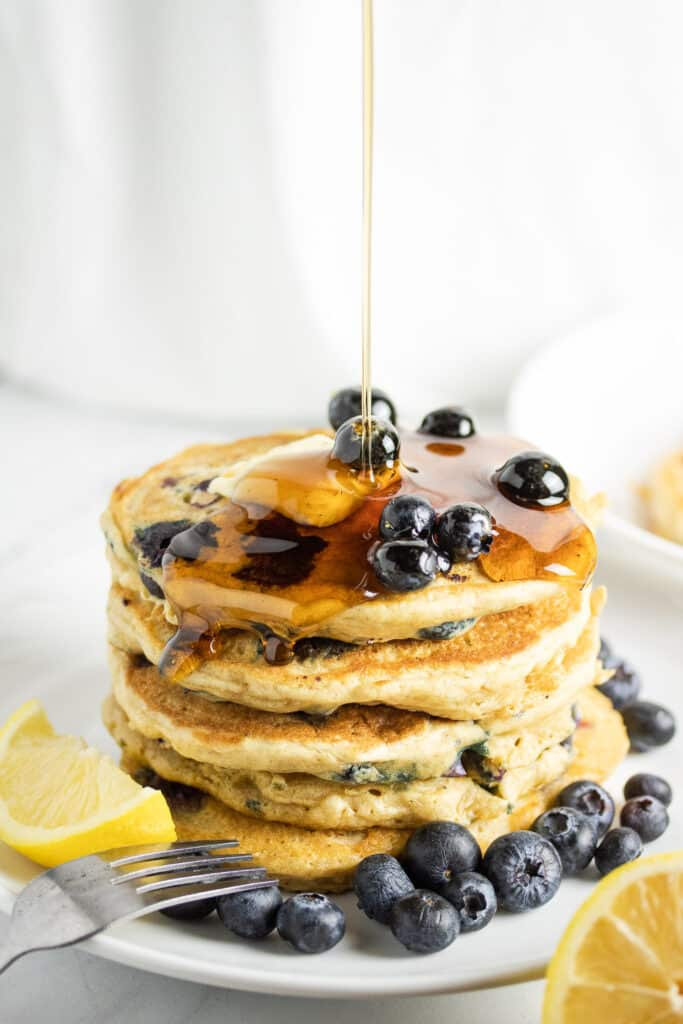 pancakes stacked on top of each other on a white plate topped with fresh blueberries and syrup drizzle down on top