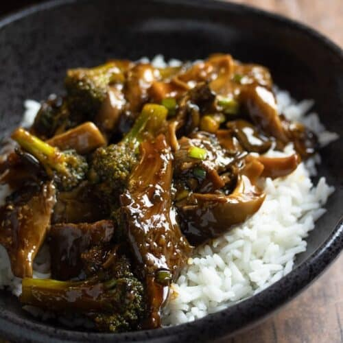 teriyaki oyster mushrooms and broccoli over white rice in a black bowl