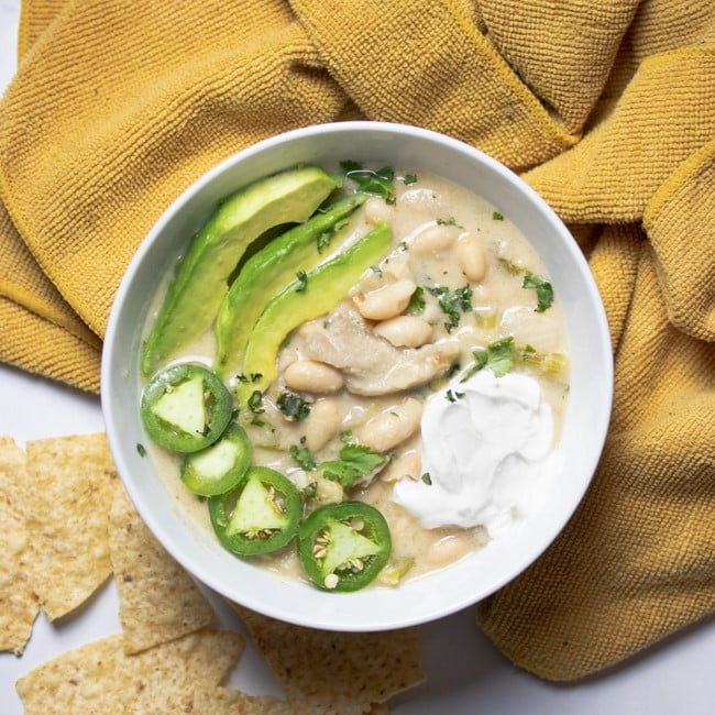 white chili in a white bowl topped with avocado slices, jalapeno slices, and vegan sour cream