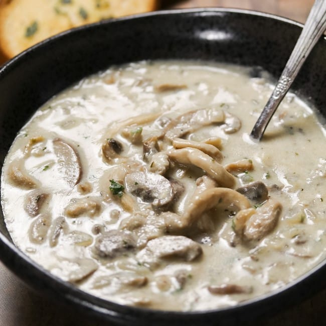 cream of mushroom soup in a black bowl with spoon in it