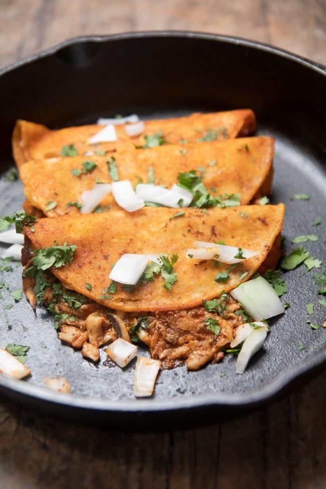 3 birria tacos in a cast iron pan