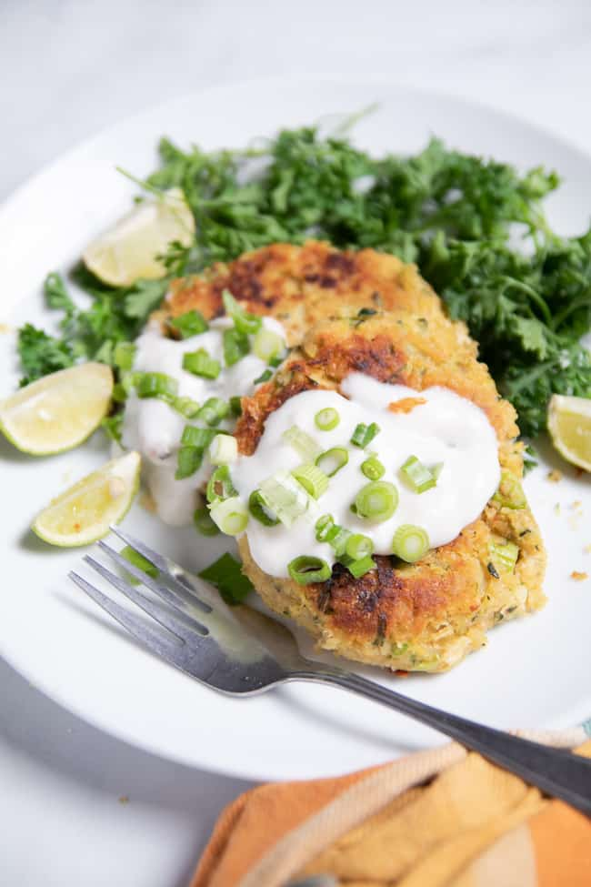 2 zucchini fritters on a plate topped with yogurt and green onions