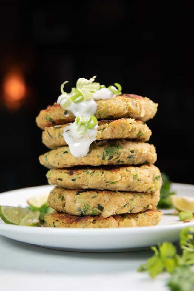 zucchini fritters stacked on top of each other topped with yogurt and green onions